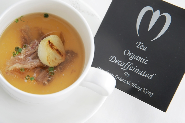 A full-bodied consommé with a specially prepared tea bag of dried flower petals and gold flake
