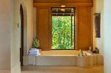 The expansive, terrazzo-tiled bathroom comes with a shower and deep soaking tub, a window-side divan, double terrazzo vanities and twin coconut-wood dressing areas.