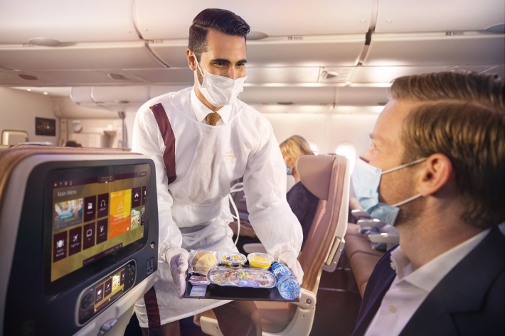 Etihad Crew onboard with PPE serving guests